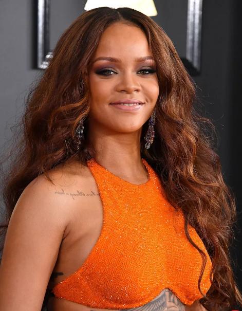 Rihanna con vestido naranja y tono de cabello cinnamon