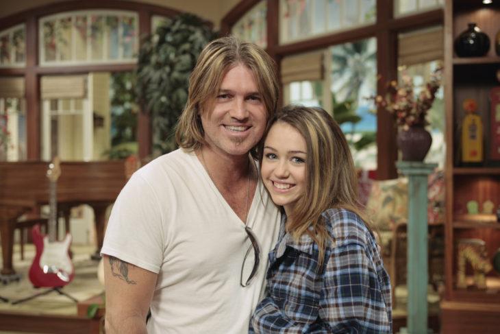 Billy Ray y Miley Cyrus abrazados, sonriendo en un set simulador de la sala de la casa de Hannah Montana