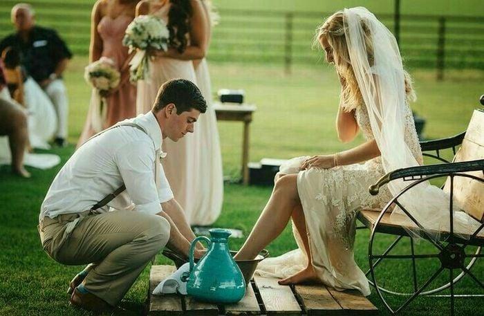 Pareja de novios lavandose lso pies en Ceremonia del lavatorio de pies