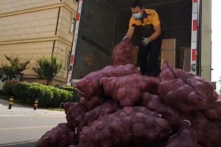 Hombre descargando costales de cebolla morada