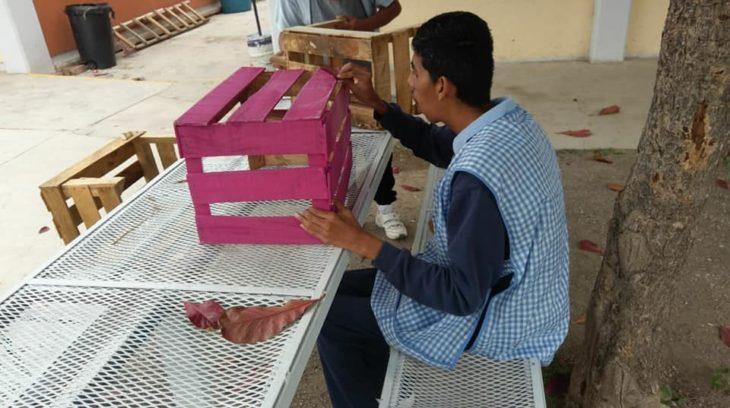 Elías pintando la reja de madera