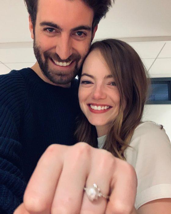 Emma Stone y Dave McCary mostrando su anillo de compromiso, abrazados y sonriendo