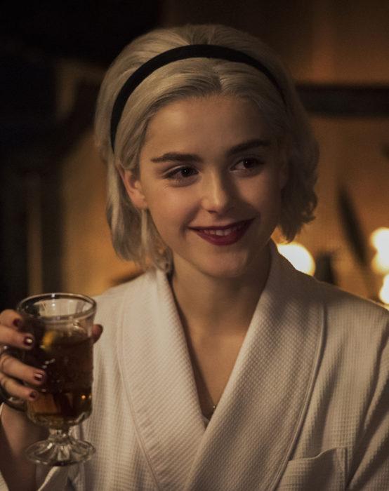 Personaje de las aventuras de sabrina usando una diadema negra y bebiendo