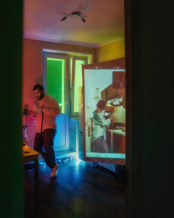 Fotógrafo Karman Verdi junto a un proyector reflejando a una chica cocinando