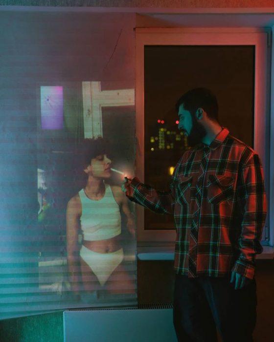 Fotógrafo Karman Verdi junto a una manta con un proyector fumando un cigarrillo