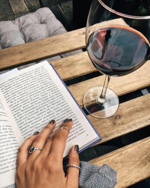 Mujer leyendo libro con copa de vino tinto