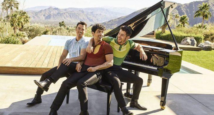 Kevin, Joe y Nick Jonas sentados en un piano al aire libre