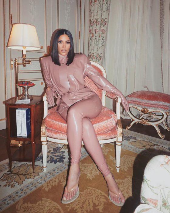 Kim Kardashian usnado conjunto de vinil sentada en una silla