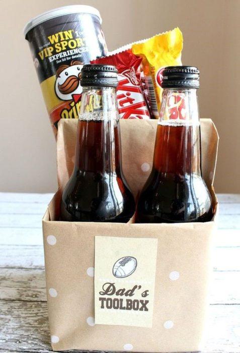 Caja de cartón con forma de six pack de cerveza llena de papas fritas y chocolates