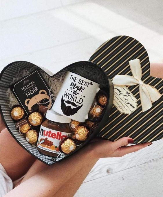 Caja en forma de corazón rellena de chocolates, nutella y una taza blanca
