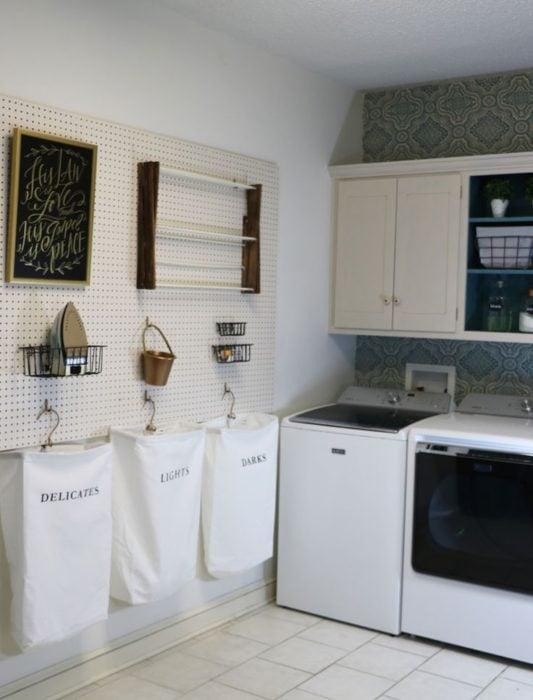 Cuarto de lavandería con sacos para la ropa sucia en la pared