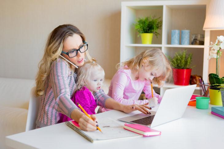 Mamá realizando trabajo en casa junto con sus hijos