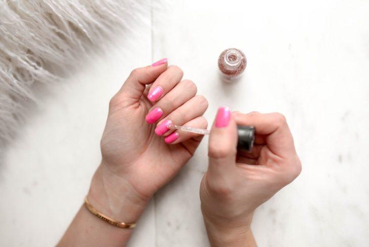 Chica pintando sus uñas en color rosa