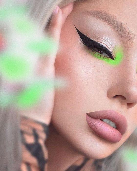 Chica con delineado negro y un toque de sombra verde fosforescente en el lagrimal