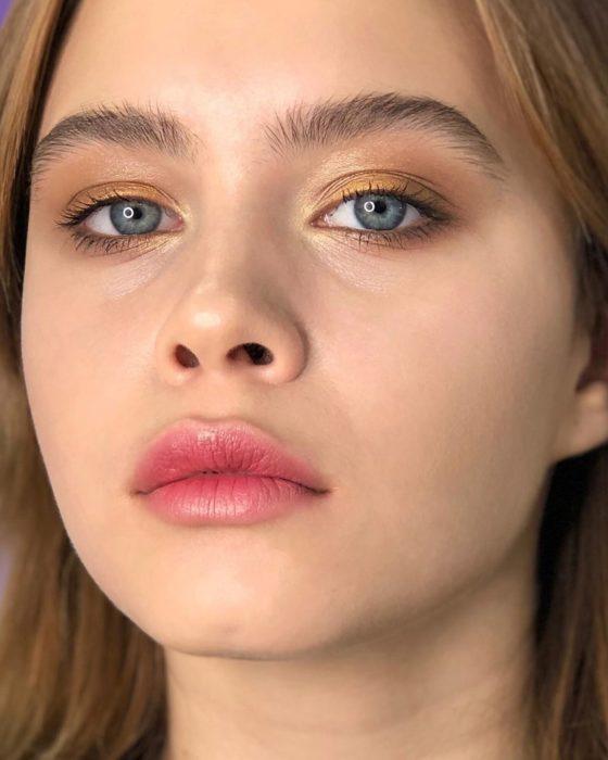 Chica de ojos azules con tinta de labios muy sutil color roja