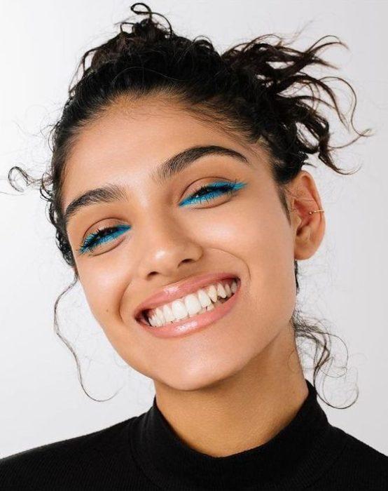 Chica morena con cabello agarrado en un chongo con delineado azul en los ojos
