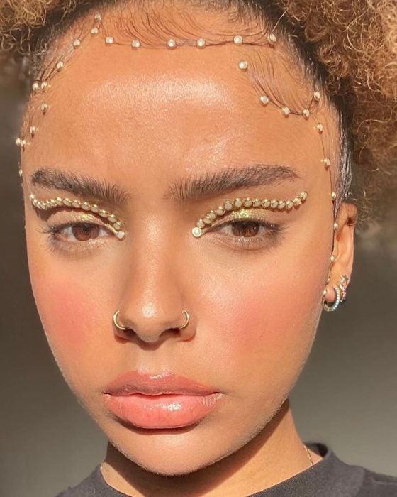 Chica morena con piedritas doradas en los parpados como maquillaje