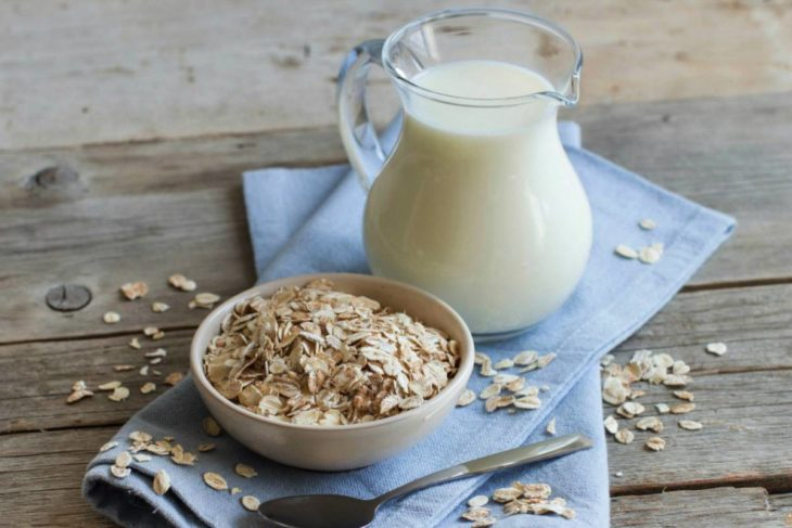 Bowl with oatmeal and a jug of fresh milk