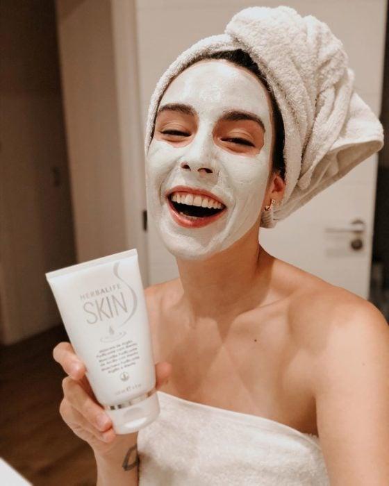 Mujer aplicando mascarilla en su rostro