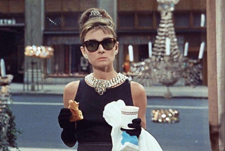 Audrey Hepburn usando un vestido negro en la película Desayuno con diamantes