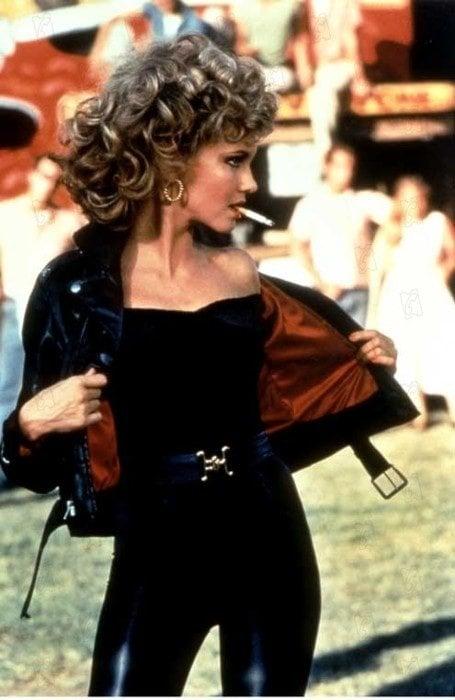 Olivia Newton John usando un traje negro en la películaVaselina