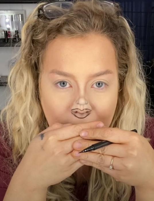 Mujer dibujando unos labios pequeños sobre su nariz