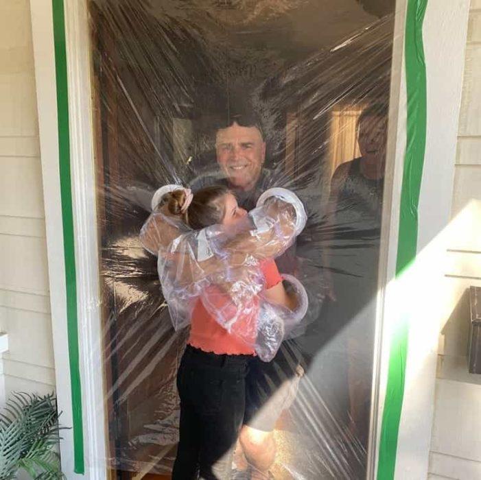 Niña abrazando a sus abuelos a través de una puerta de plástico