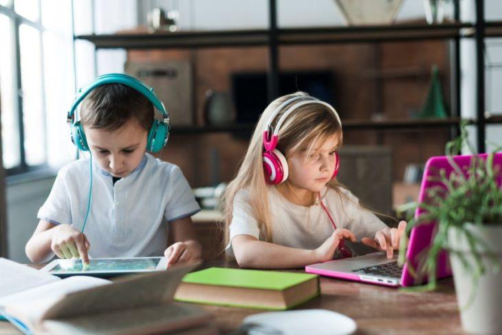 Niños rubios con audífonos grandes y tablets en clases online