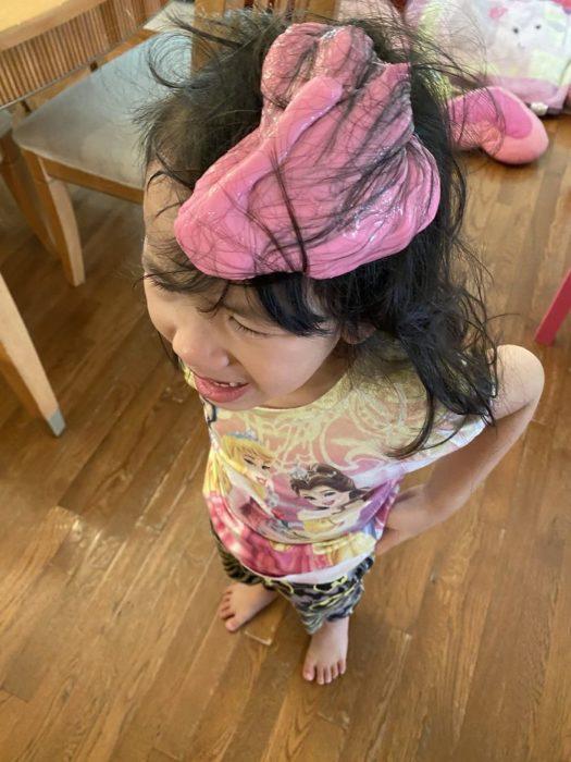 Niña con el cabello lleno de slime de color rosa