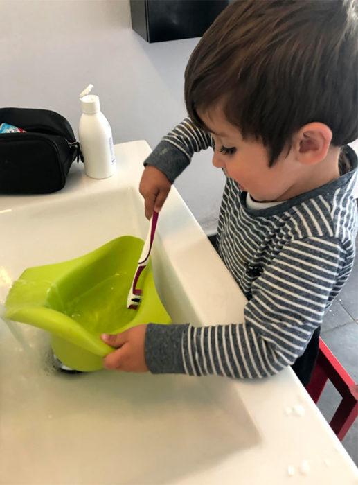 Niño lavando el orinal con el cepillo de dientes