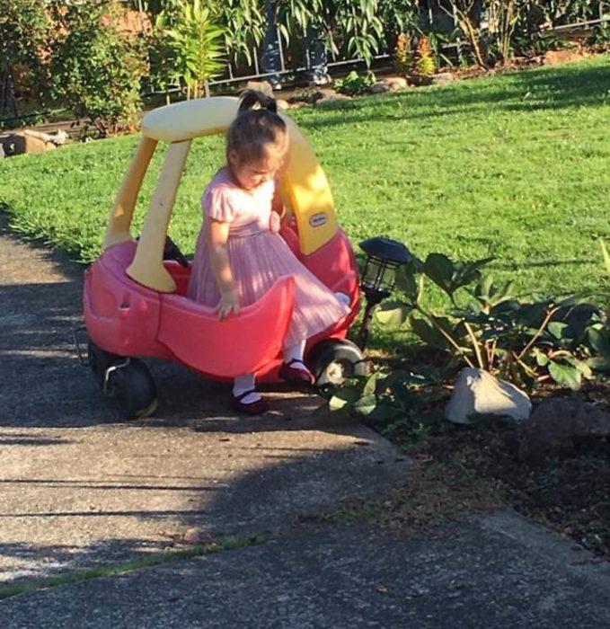 Niña huyendo del jardín al golpear una lampara con su auto de juguete
