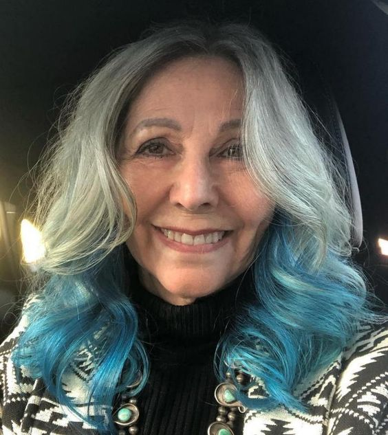 Older woman with long gray hair and blue tips