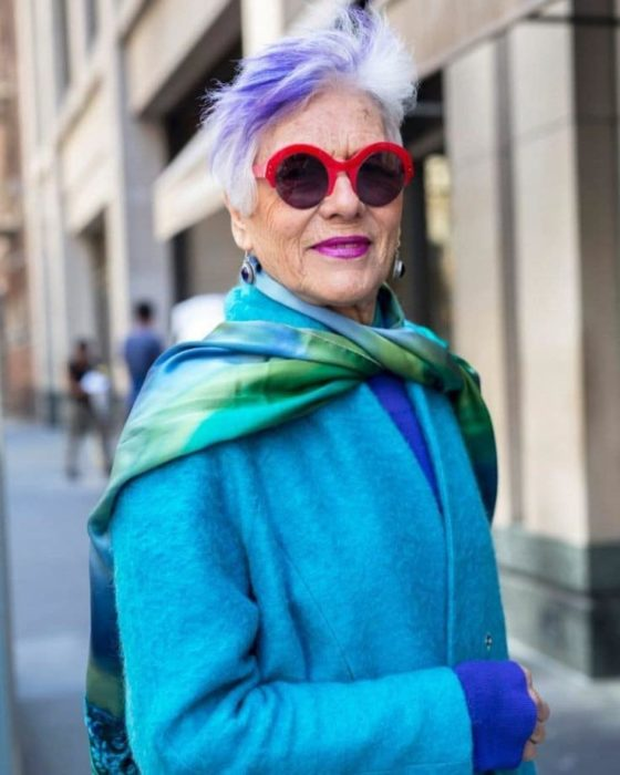 Mature woman with blue jacket and short gray hair with purple streak