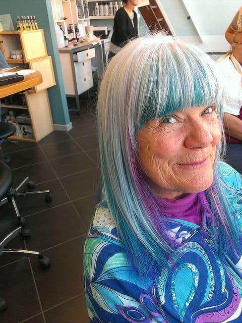Mature woman with medium hair with gray hair and blue and purple colors