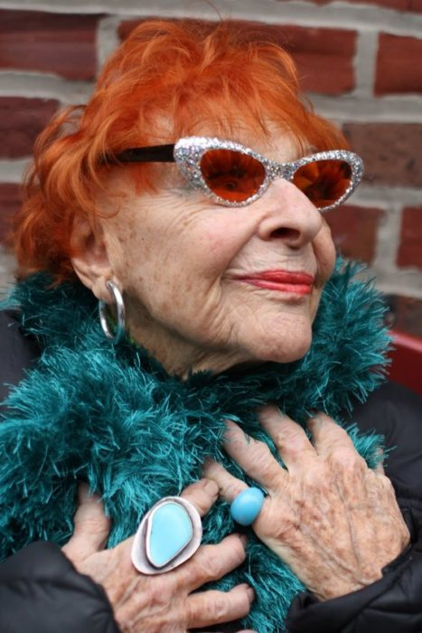 Elderly woman with turquoise scarf and vibrant orange colored short hair