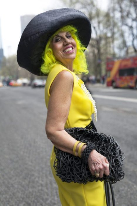 Older woman in yellow blouse and black hat with phosphorescent green hair