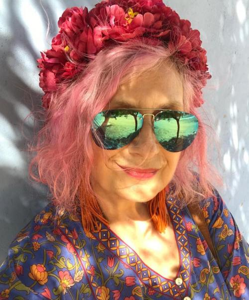 Mature woman with short pink hair and flower crown