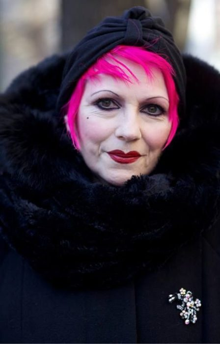 Mature woman in black coat and hat and short fuchsia hair