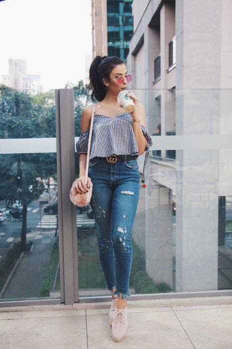 Chica usando un outfit inspirado en Lara Jean con jeans, blusa sobre los hombros y tenis de color rosa