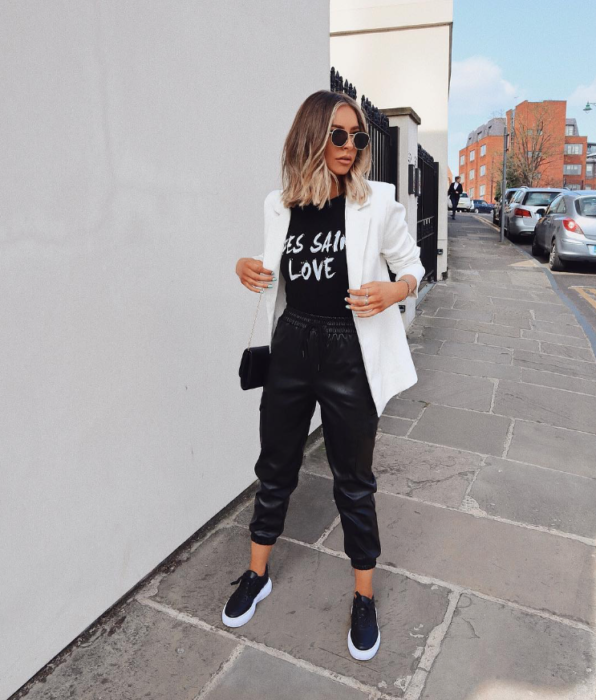 Chica usando un outfit inspirado en Lara Jean con un traje de color negro y blazer de color blanco