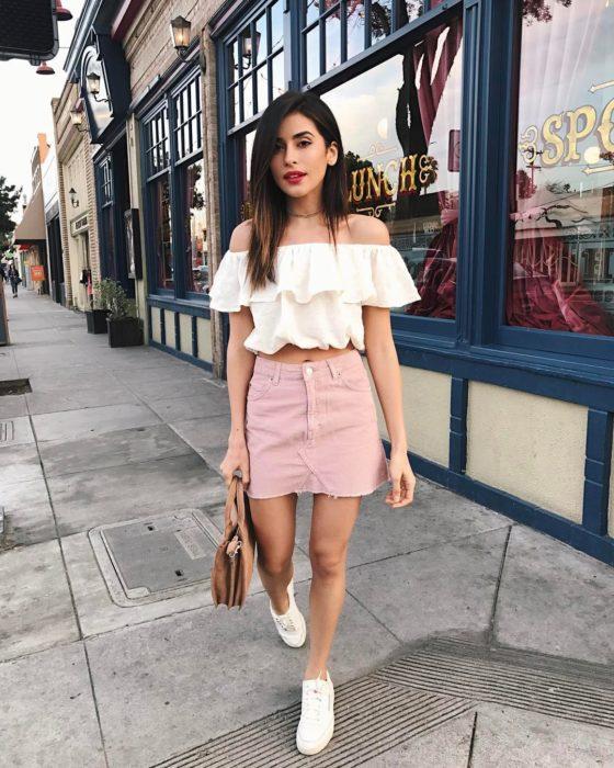 Chica usando un outfit inspirado en Lara Jean con una falda de color rosa, tenis y blusa blanca