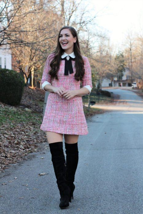 Chica usando un outfit inspirado en Lara Jean con vestido de cuadros color rosa y botas negras altas