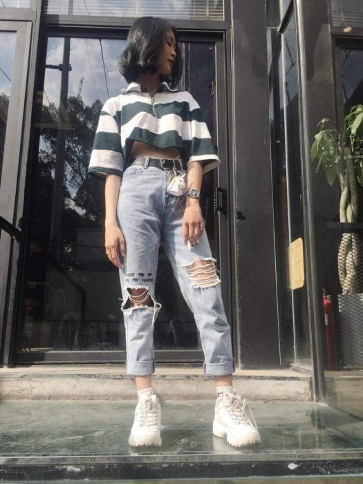 Chica usando un outfit inspirado en Lara Jean con jeans, blusa ombliguera y tenis
