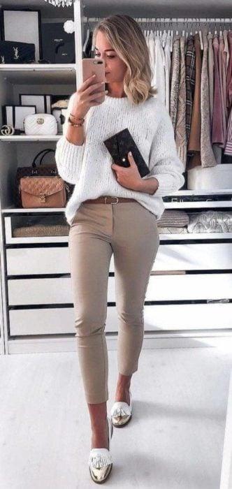 Chica rubia con suéter blanco y pantalón beige tomándose una foto frente al espejo