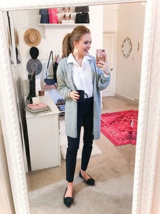 Chica se toma selfie frente al espejo con cardigan gris, blusa blanca y pantalón negro