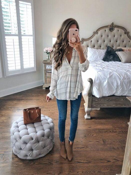 Chica de cabello largo y rizado se toma selfie frente al espejo con blusa a cuadros delgada con jeans