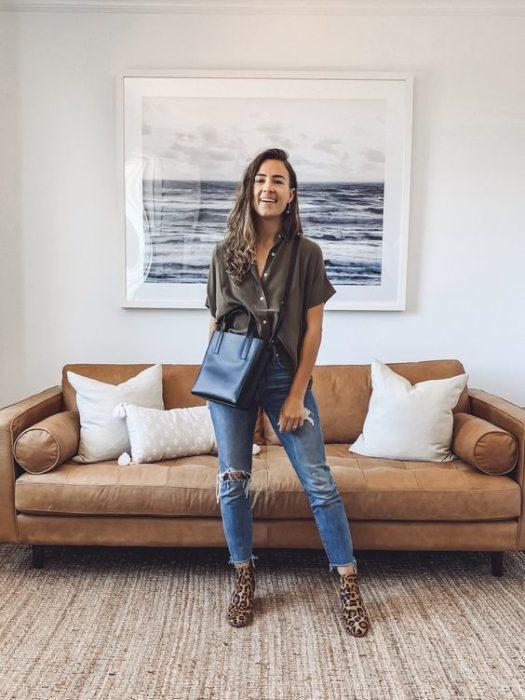 Chica posa en la sala de su casa con jeans, bolsa negra grande y blusa verde