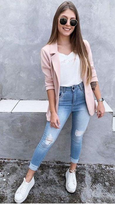Chica castaña de pelo largo y suelto usa lentes oscuros y viste jeans claros, blusa blanca y saco rosa claro