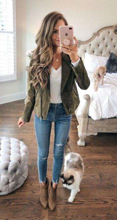 Chica castaña de cabello largo y rizado se toma selfie frente al espejo mientras viste saco verde militar, blusa blanca y jeans