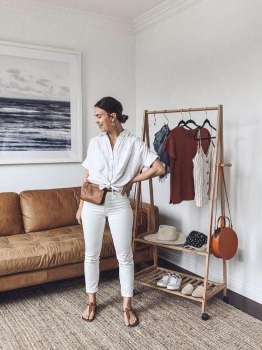 Chica posa con mano en la cintura con blusa y pantalón blancos y una cangurera café